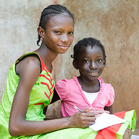 Courtesy of istock, Two African girls look at camera, one is writing