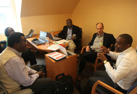 Five men in an office collaborate and discuss in an office at the Center for Global Health Studies
