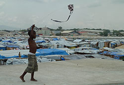 Photo courtesy of CDC, CC BY 2.0, Boy flies a kite, refugee camp in background, after 2010 earthquake in Haiti