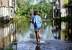 Woman walks through flooded street, water up to her ankles, 2-story wooden buildings on either side of street