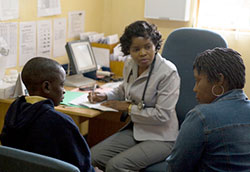 A medical professional takes notes during a discussion with a young child and a caregiver in a clinic.