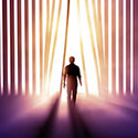 Silhouette of person walking through vertical blinds toward a bright light