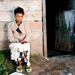 Photo by subman/iStock/Thinkstock. Xhosa woman in front of home in South Africa.