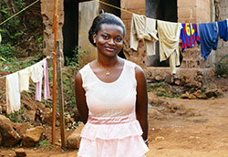 Photo by SylvieBouchard/iStock/Thinkstock, Well dressed young African woman stands outside, laundry hanging on line in background