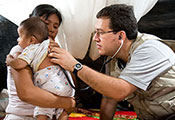 Doctor puts stethoscope on baby's back while mother holds the baby, all seated on ground, tarps in background