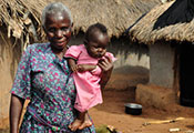 Older woman holds baby outdoors, thatched huts in the background