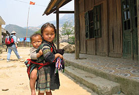 Young Vietnamese girl with boy toddler strapped to her back, standing in front of wooden house on dry dirt ground.