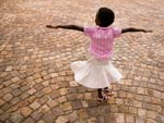 young girl in skirt twirls on brick-paved street, arms fully extended