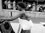 Young Ugandan woman, holding and looking at piece of fabric, with baby tied to her back, baby looks straight at camera