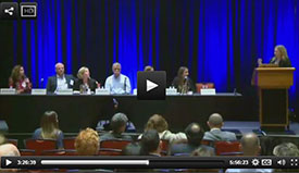 Screen capture of webcast of a speaker on a stage at a podium engaging with 6 panel members