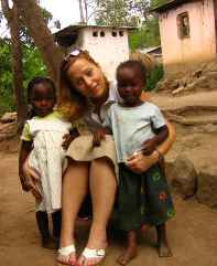 Gretchen Birbeck posing with two little African girls