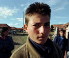 Young Bulgarian man looks into camera, village buildings and other people in background