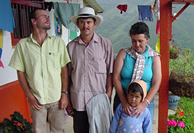 A family in Colombia on the porch, mountains in background.