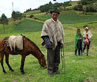 In lush green mountains of Colombia, a man looks at the camera holding the reigns of a horse, women in background