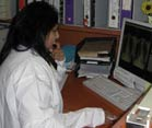 Dr Naidoo in a white lab coat seated at a desk reviews side by side chest x-rays on a computer screen