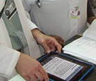 iPad, held by hands or person wearing white lab coat, placed on desk next to paper file