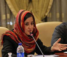 Iranian woman wearing head scarf seated at conference table, woman speaks into microphone