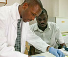 Two men working side by side in a laboratory at a MEPI-supported institution examine samples, one wears white lab coat and glove