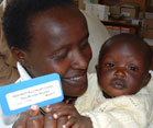 A Kenyan woman holding a baby holds up a blue and white patient ID card