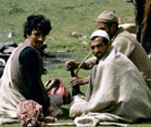 Indian men sit on the grass in a field, one smokes a water pipe