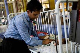 Male doctor sits on edge of crib with lowered rail, uses stethoscope to examine baby