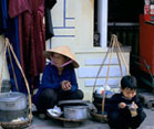 Vietnamese woman and child crouche next to pots on the sidewalk