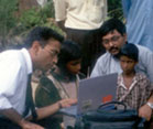 Outdoors, child seated at laptop is instructed by man in shirt and tie, adult and another child look on close by