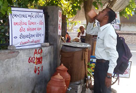 In India, a man drinks from a cup at a public outdoor drinking water station in the shade on a street corner.