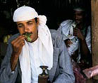 Man with droopy eyes stuffs handful of khat into his mouth
