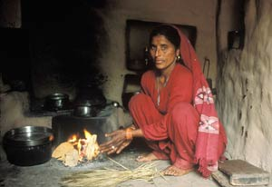woman, barefoot, squats on the floor next to a cooking fire, dark smoke fills the air, no visible chimney or ventilation