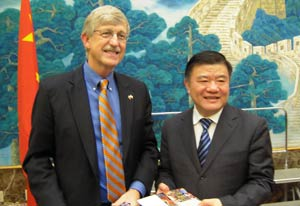 Dr Francis Collins and China health minister Chen Zhu stand side by side, smiling for camera, each holding a gift