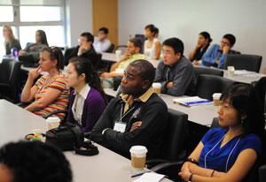 Conference attendees seated in full classroom listen attentively to speaker