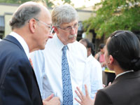 Dr Roger Glass and Dr Francis Collins listen attentively to woman speaking, her back to the camera, outdoors