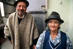 Older man and woman stand side by side facing camera, both smilin