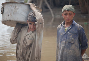 Two young men, mud on their shirts, stand in front of murky brown water, one holds large bucket on his shoulder