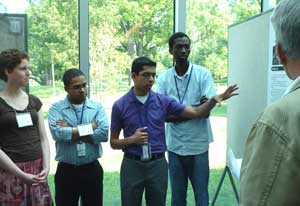 Sujal Parikh points to a mounted conference poster, four peers, all wearing conference badges, look on