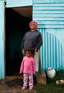 African mother and young daughter stand in front of their home