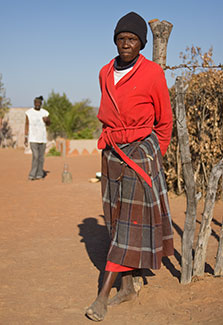 Older African woman stands outside