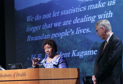 Dr. Agnes Binagwaho speaking at a podium, Dr. Francis Collins looks on, slide projected in the background