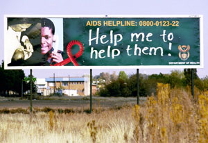 Large outdoor billboard surrounded by grass reads AIDS Helpline, Help me to help them!