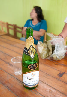 Partially empty bottle of champagne sits on table next to empty cup