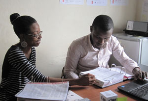 Dr. Juliana Anyanwu seated at a desk reviews large binders full of data, man seated next to her enters data on a laptop