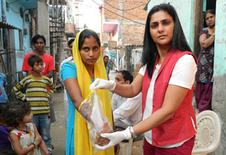 Dr. Arti Kundu collects samples from hand surfaces using a bag of sterile water from a female study participant in a busy street