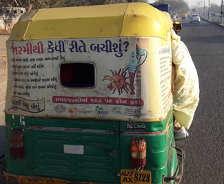 Back of an auto rickshaw on a street in India, advertisement on back includes public health message on extreme heat