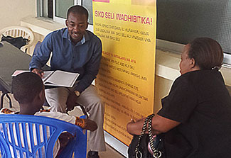 Dr. Emmanuel Balandya talks with young patient and parent who are seated across from him