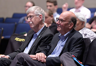 Dr. Francis S. Collins and Dr. Roger I. Glass attentively watch the Barmes Global Health Lecture from seats in the auditorium.
