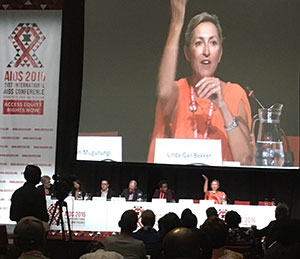 Linda-Gail Bekker speaks from a long table during a panel presentation at AIDS 2016, a close up projected on the screen behind her