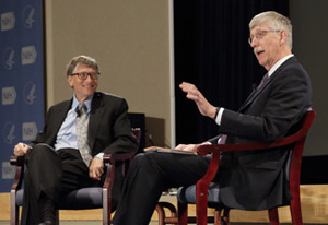 Francis Collins, speaking and gesturing with hands, seated on stage across from Bill Gates, smiling