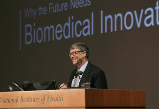 Bill Gates, smiling, stands at podium, podium reads National Institutes of Health, slide projected in background