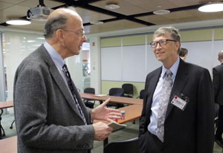 Roger Glass speaks with Bill Gates in small conference room